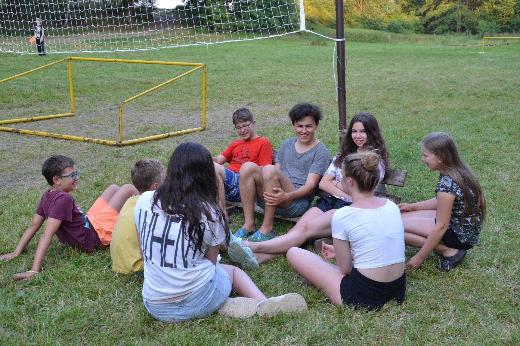 Rodilý mluvčí hovoří se skupinkou starších dětí na letní táborě s angličtnou a příběhem