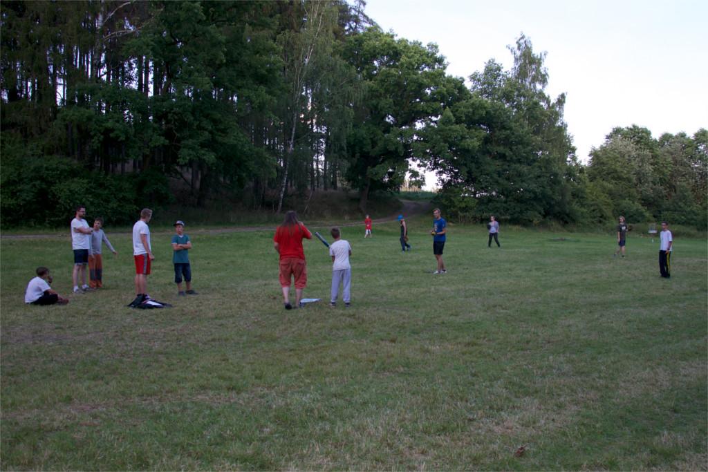 Táborníci hrající softball během sportovních táborových aktivit