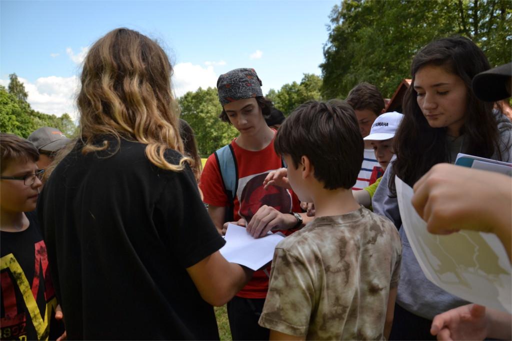 Začátek odpolední hry. Táborníci fasují mapy, podle kterých se budou později muset orientovat.